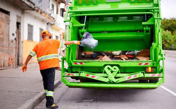 бросает мусор в мусоровоз